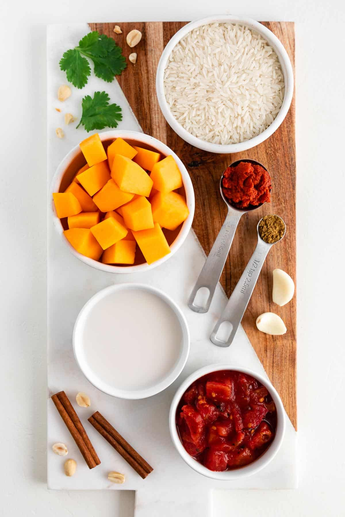 a marble and wood cutting board topped with bowls of coconut milk, diced tomatoes, squash, white rice, cinnamon sticks, red curry paste, cumin, and cilantro
