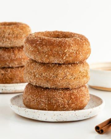 a stack of three vegan cinnamon sugar donuts on a small white ceramic plate