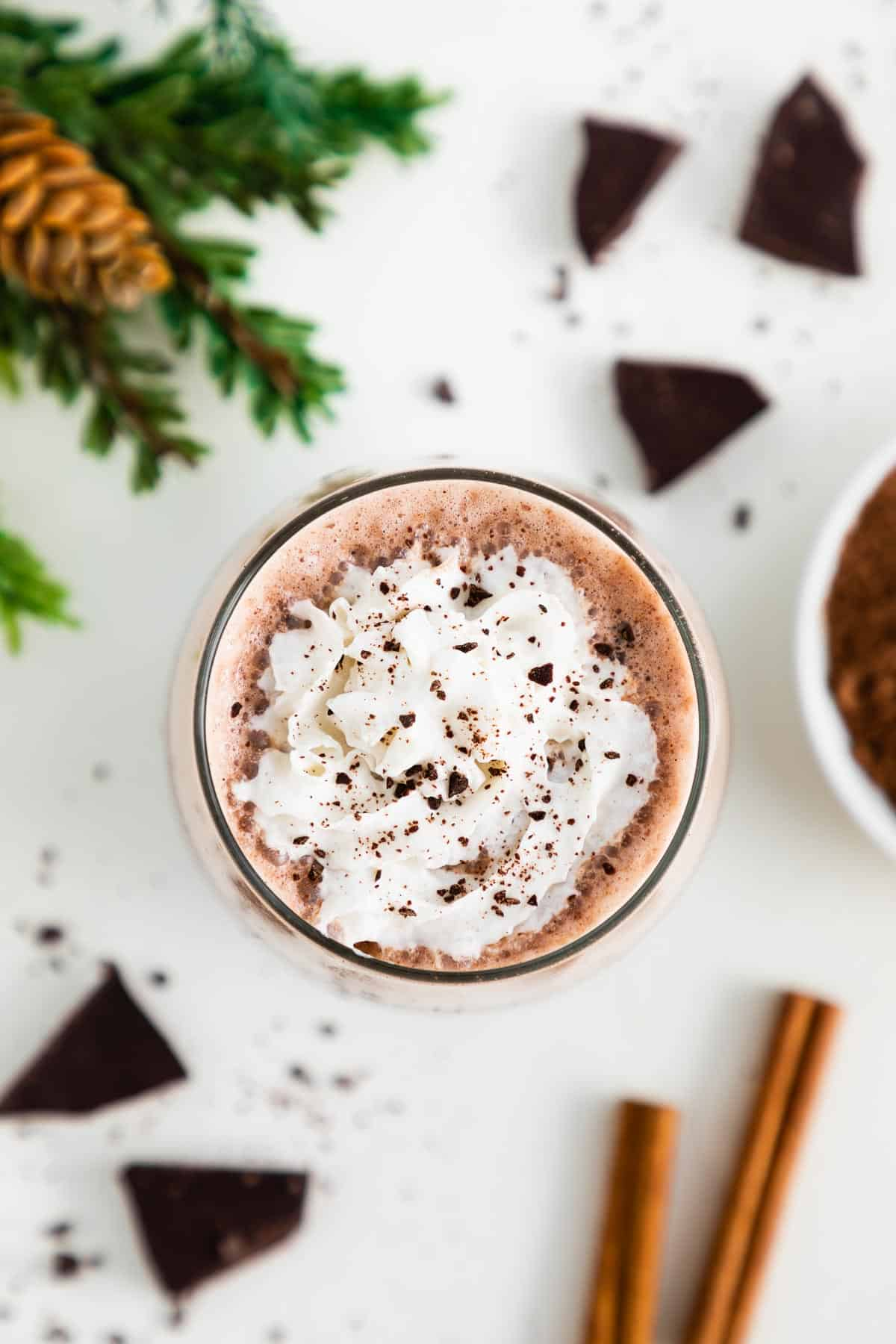 an overhead photo of vegan frozen hot chocolate in a glass with whipped cream, surrounded by pieces of dark chocolate, cinnamon sticks, and a bowl of cocoa powder