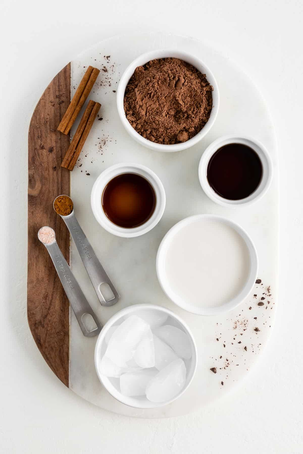 a marble and wood cutting board topped with bowls of cocoa powder, vanilla extract, maple syrup, almond milk, ice cubes, and cinnamon
