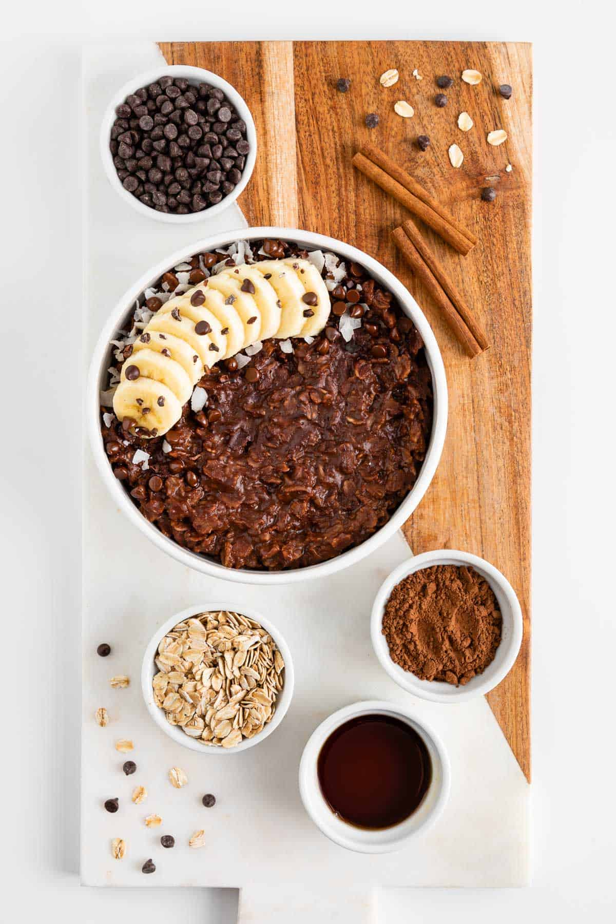 a marble and wood cutting board topped with vegan chocolate oatmeal and small bowls filled with the ingredients