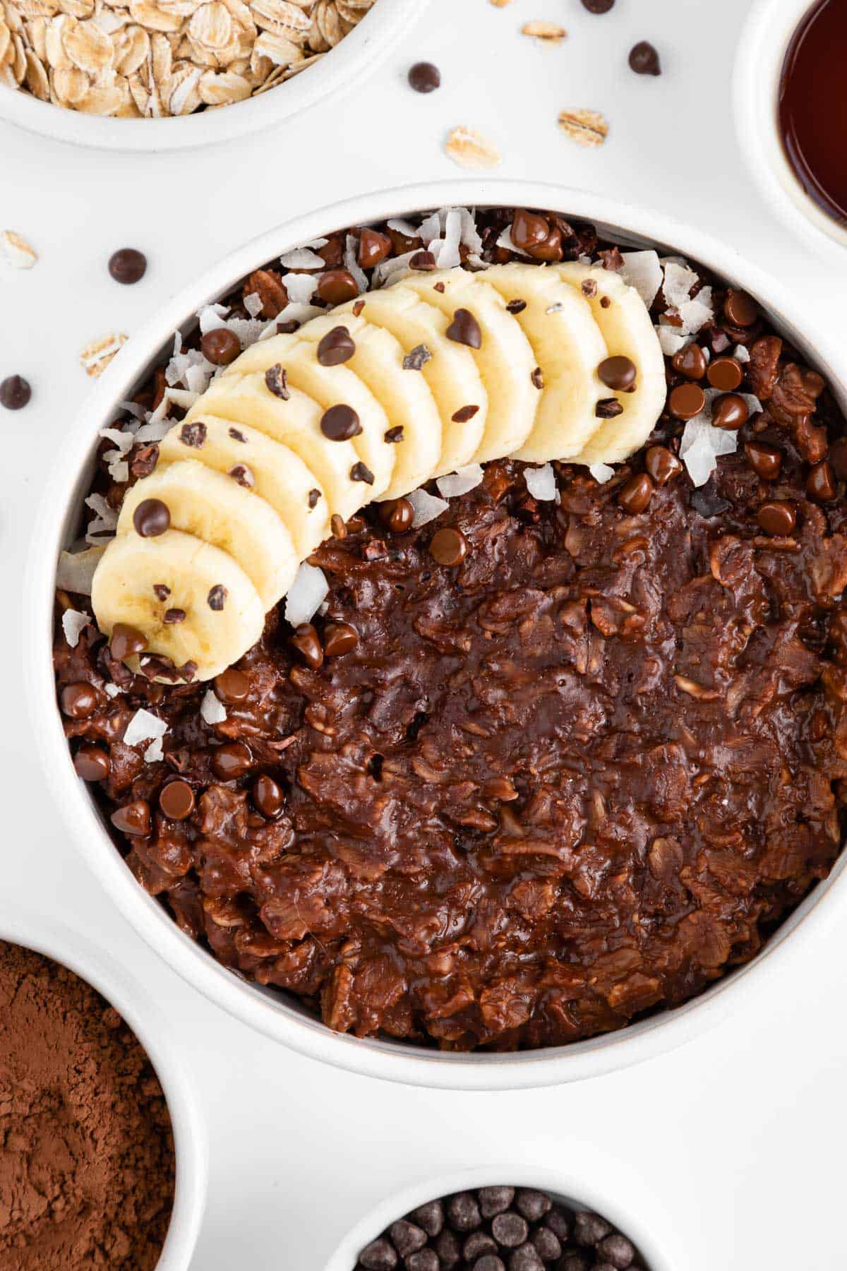 a white bowl filled with chocolate oatmeal and topped with banana, chocolate chips, coconut flakes, and cacao nibs