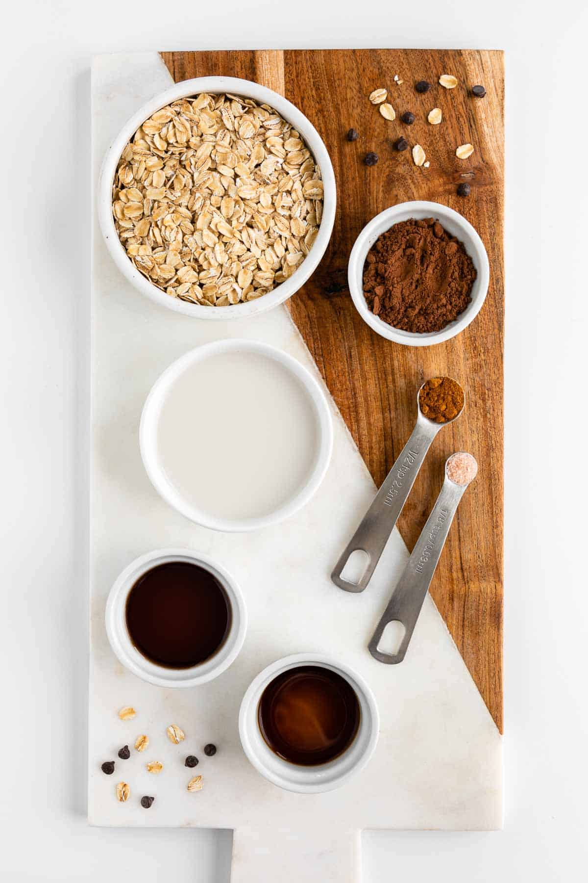 a marble and wood cutting board topped with bowls of rolled oats, cocoa powder, almond milk, maple syrup, vanilla extract, cinnamon, and salt