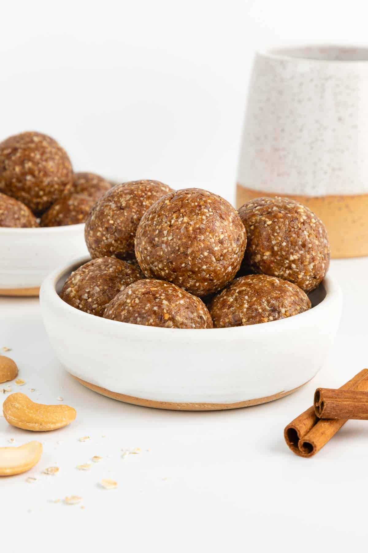 cinnamon roll energy balls stacked inside a small white bowl surrounded by cashews, oats, and cinnamon sticks