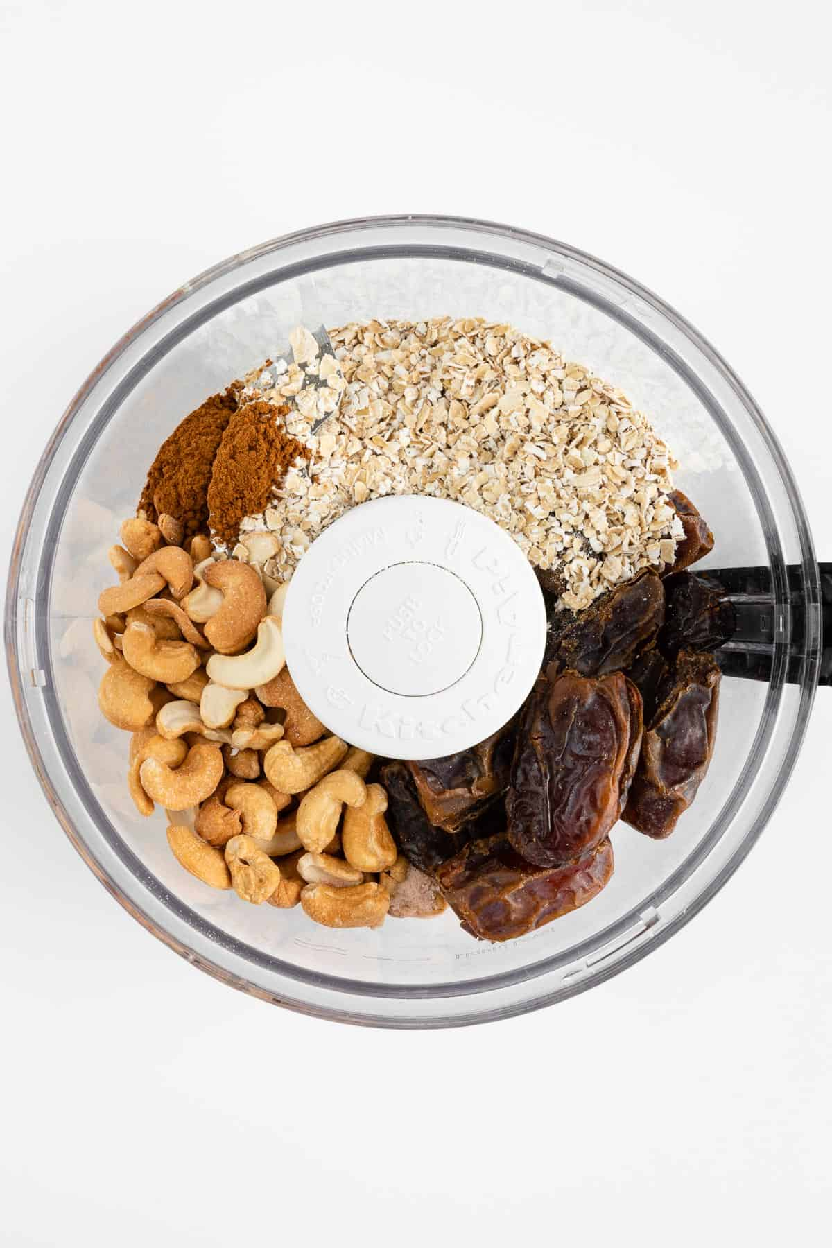 cashews, dates, oats, cinnamon, and vanilla extract inside the bowl of a food processor