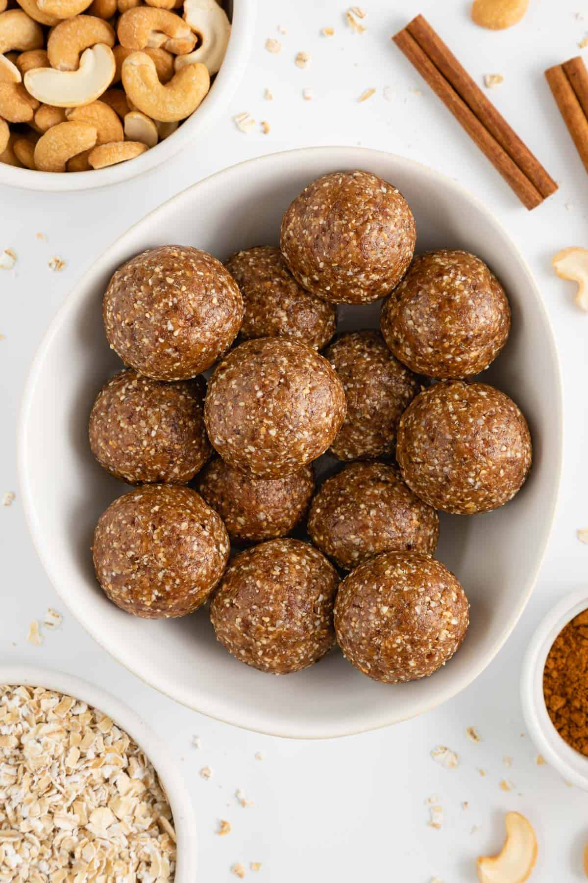 cinnamon roll energy balls inside a white bowl surrounded by oats, cashews, and cinnamon