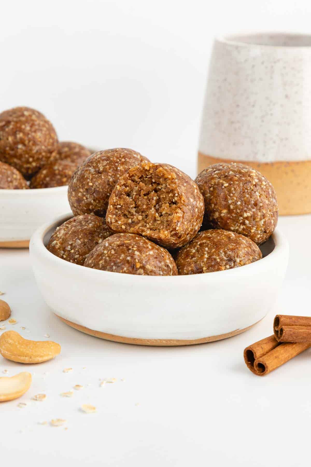 cinnamon roll energy balls stacked inside a small white bowl with a bite taken out of the middle ball