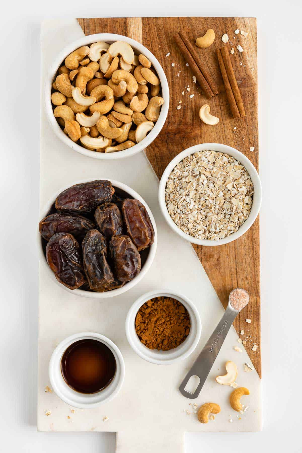 bowls filled with cashews, medjool dates, oats, cinnamon, vanilla extract, and salt on a marble and wood cutting board