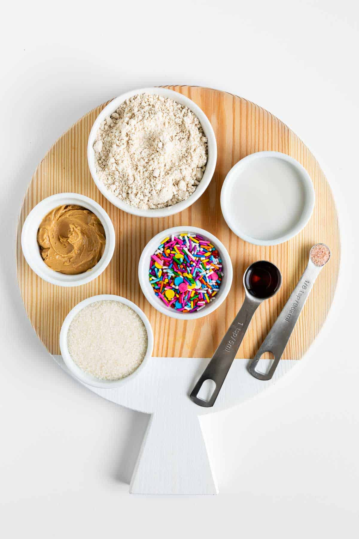 a round wooden cutting board topped with small bowls filled with rainbow sprinkles, oat flour, cashew butter, oat milk, vanilla extract, and sugar