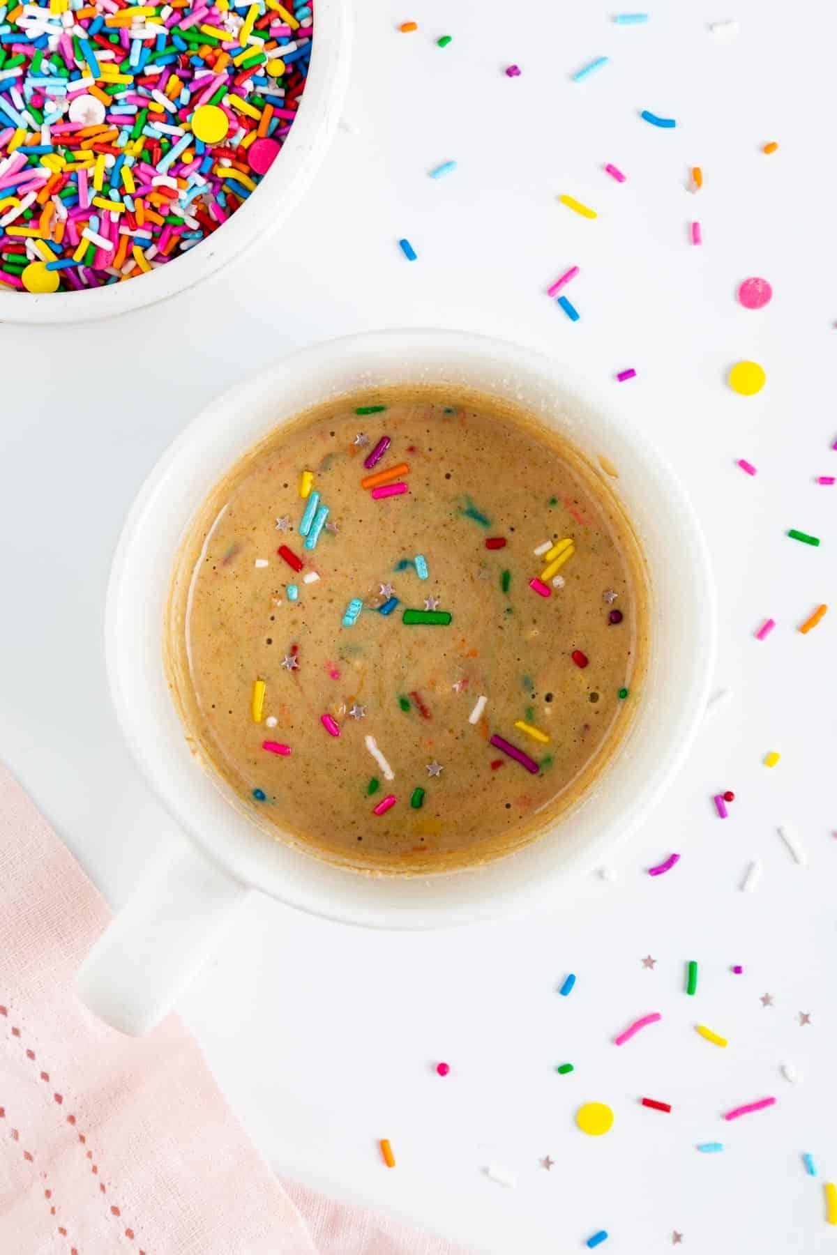 vegan cake batter inside a white mug with rainbow sprinkles