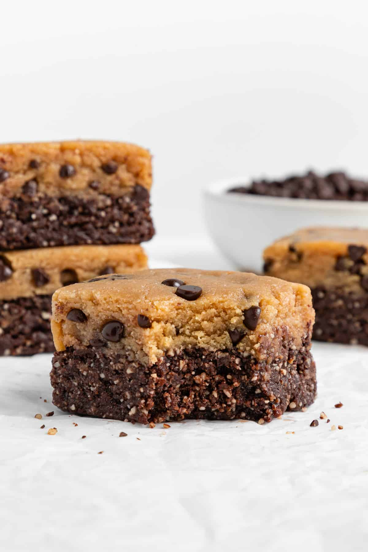 a no bake cookie dough brownie with a bite taken out of it, surrounded by more brownies