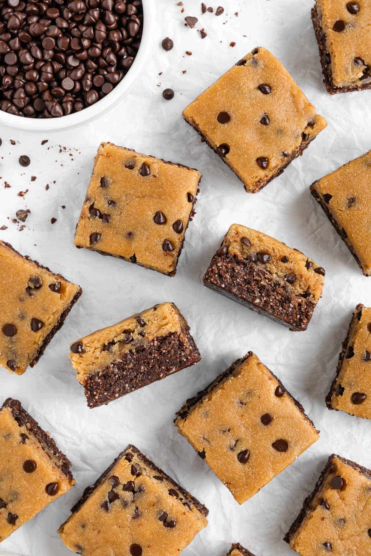 a flat-lay image of no bake cookie dough brownies on white parchment paper beside a bowl of chocolate chips