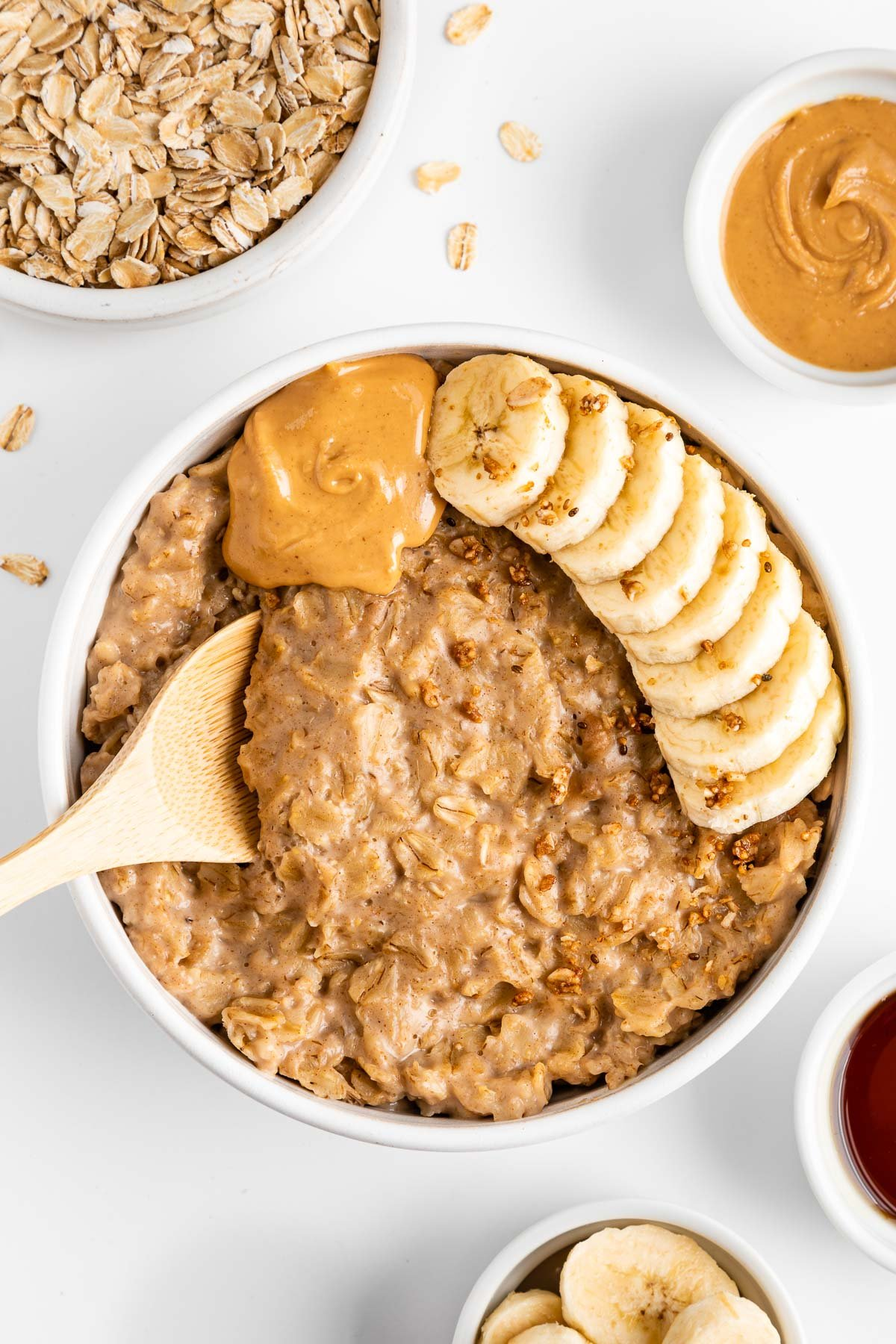 a wooden spoon scooping peanut butter oatmeal out of a bowl