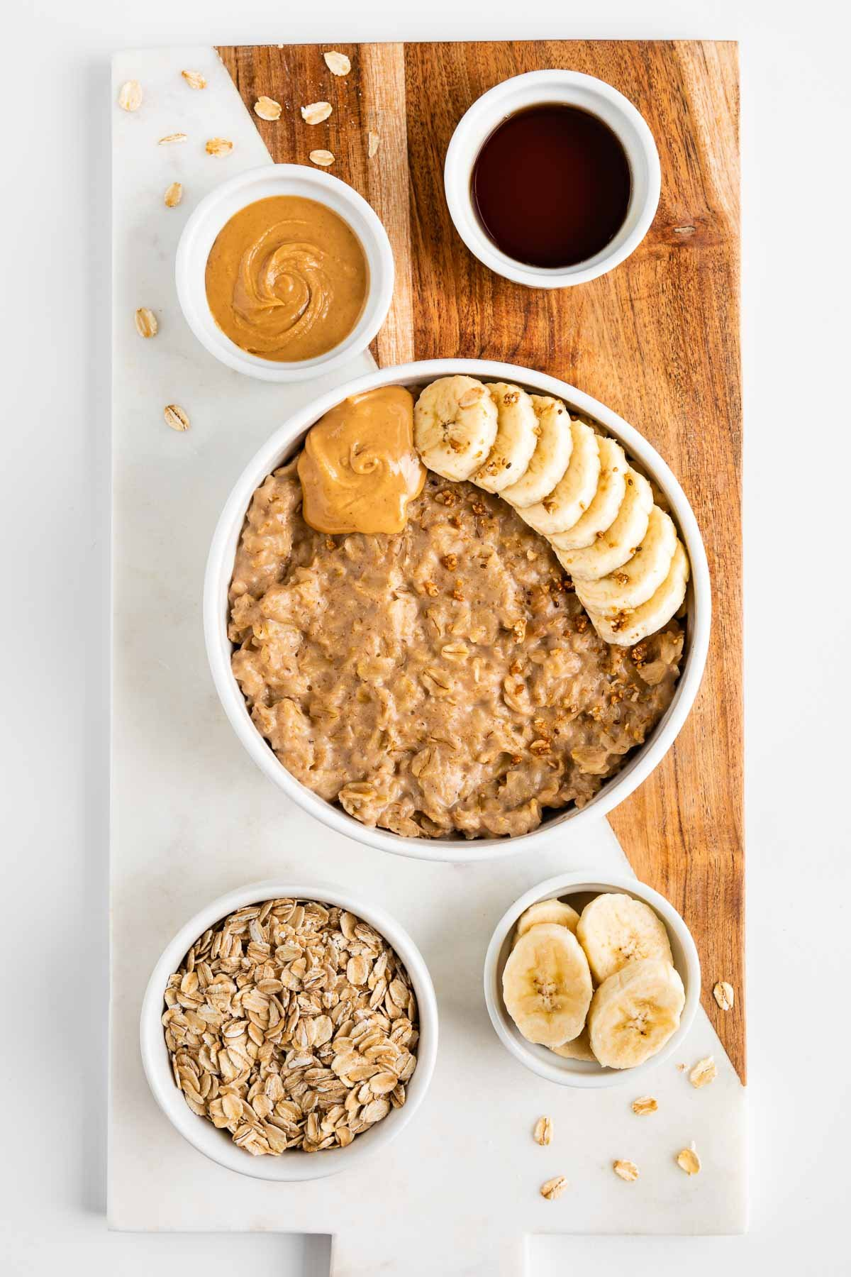 a marble and wood cutting board topped with a bowl of peanut butter oatmeal and small bowls filled with the ingredients in the recipe