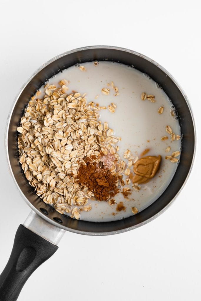 rolled oats, almond milk, cinnamon, and nut butter inside a small saucepan