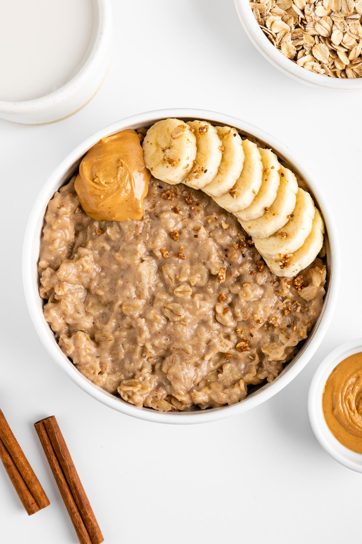 peanut butter oatmeal in a white bowl surrounded by cinnamon sticks, a bowl of oats, a bowl of nut butter, and a ceramic mug filled with almond milk