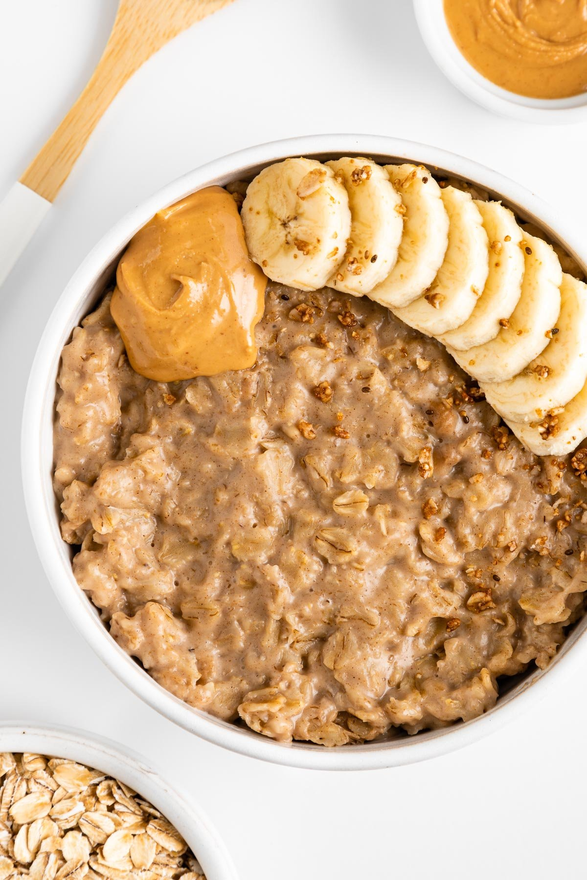 peanut butter oatmeal in a white bowl, topped with sliced banana, granola, and nut butter