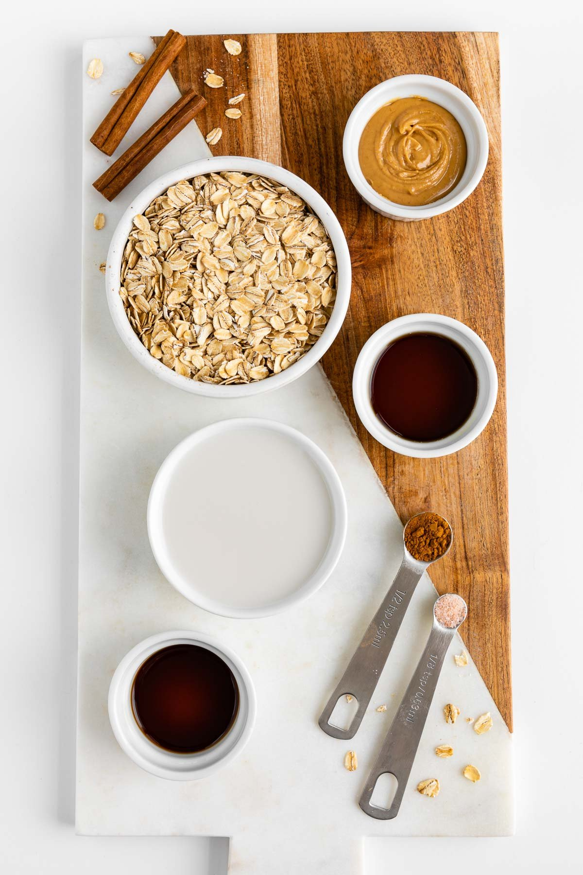 a marble and wood cutting board topped with small white bowls filled with rolled oats, peanut butter, almond milk, maple syrup, vanilla extract, and cinnamon