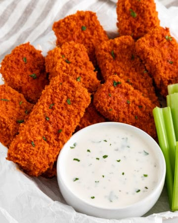 vegan buffalo tofu wings spread on a plate with celery and ranch dressing