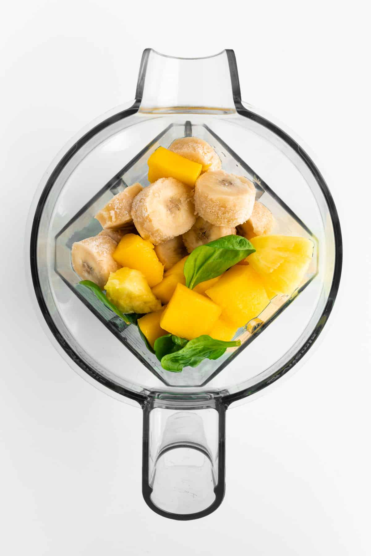 spinach, banana, mango, and pineapple inside a blender