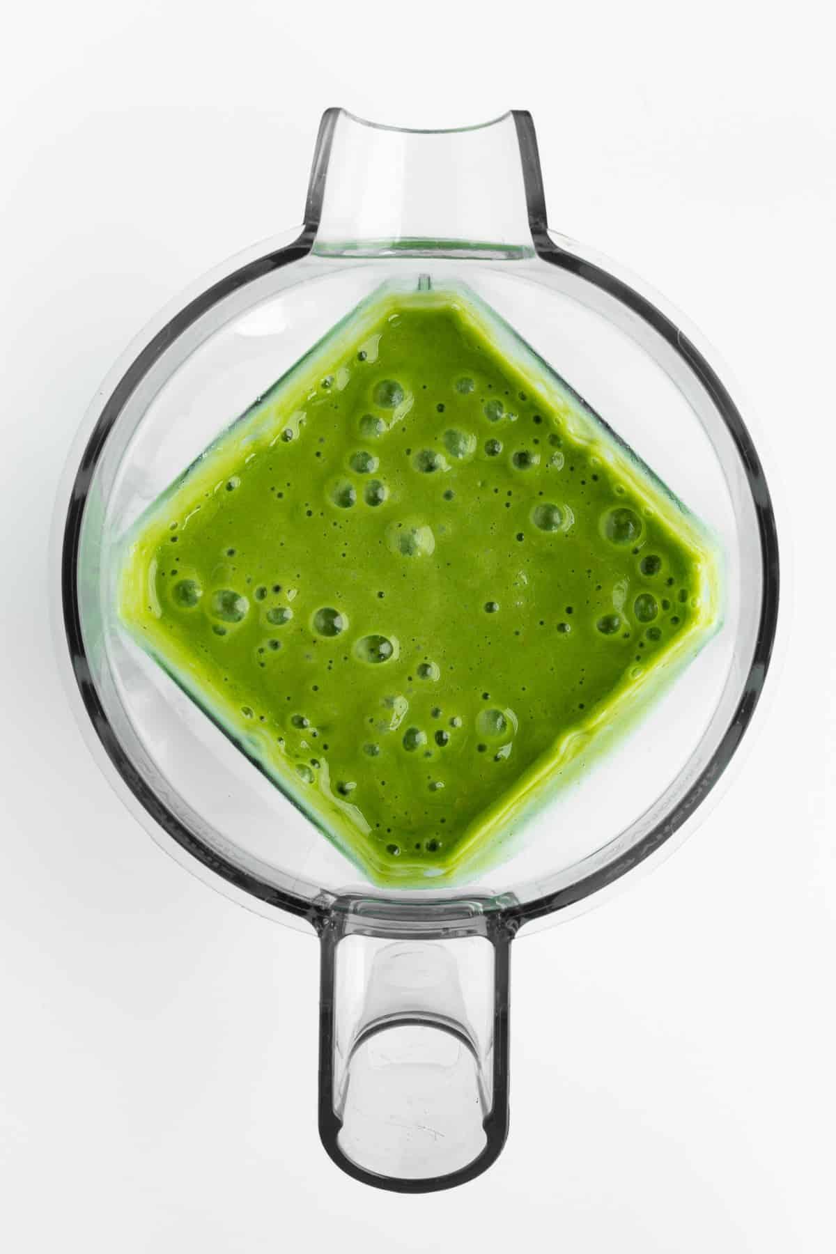 a green smoothie blended inside a blender