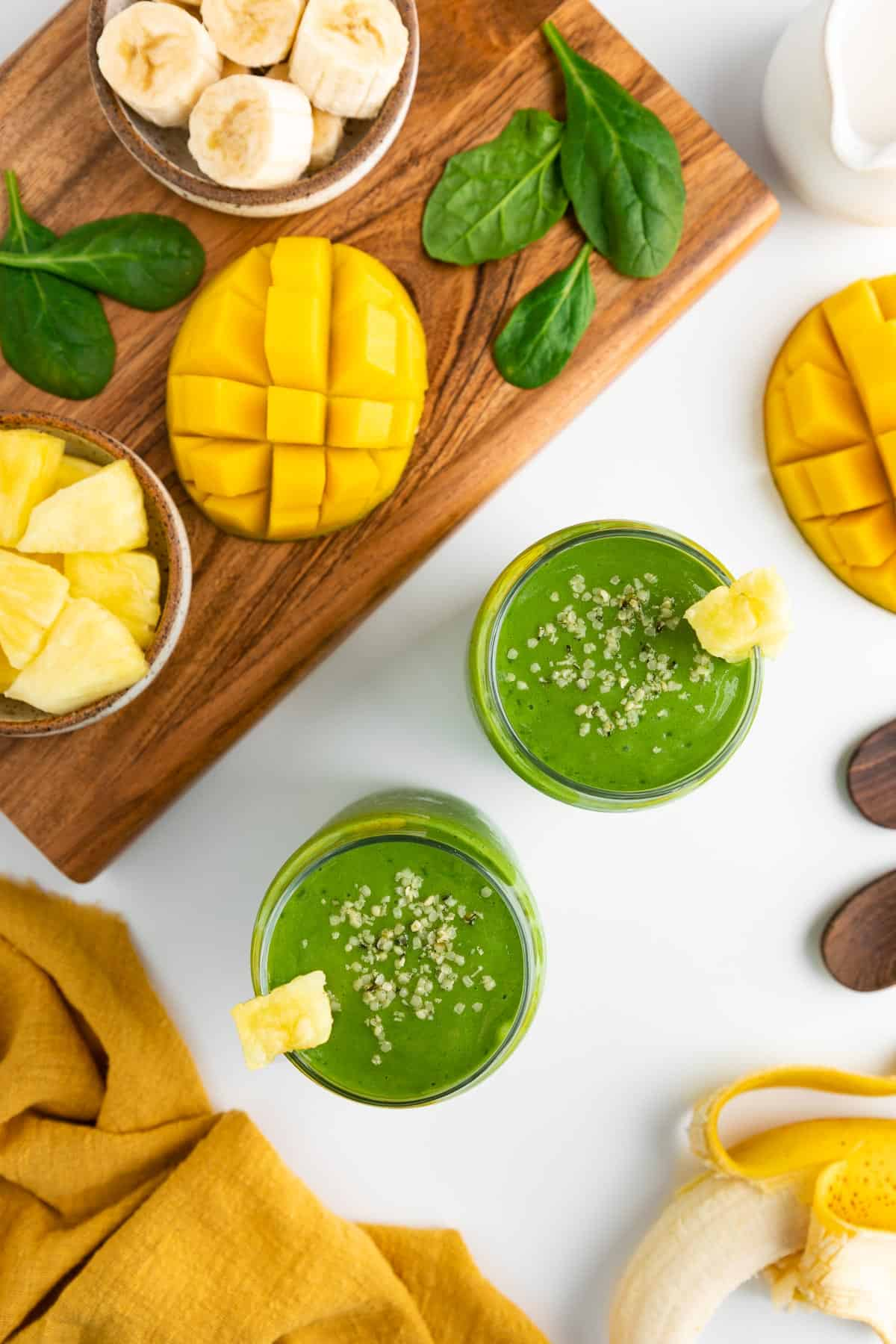 an overhead photo of two green smoothie glasses surrounded by a yellow linen napkin, a peeled banana, mango, a bowl of pineapple, and spinach leaves