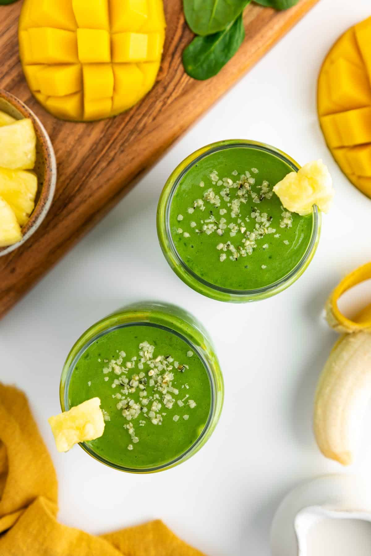 an overhead photo of two green smoothies in glasses, surrounded by sliced mango, pineapple chunks, a peeled banana, spinach, and a yellow linen napkin