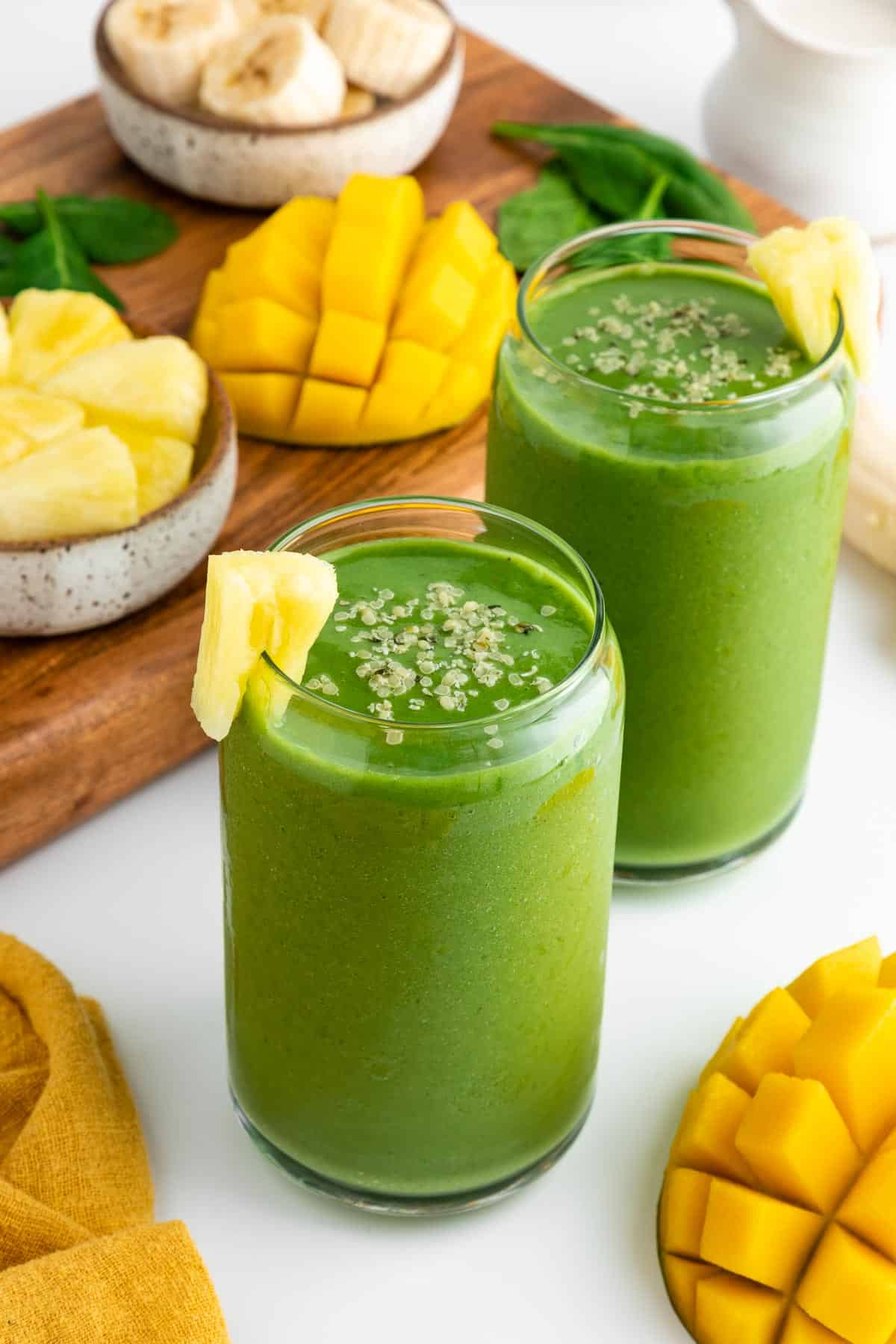 two glasses filled with a green smoothie surrounded by fresh mangoes, banana, pineapple chunks, and spinach