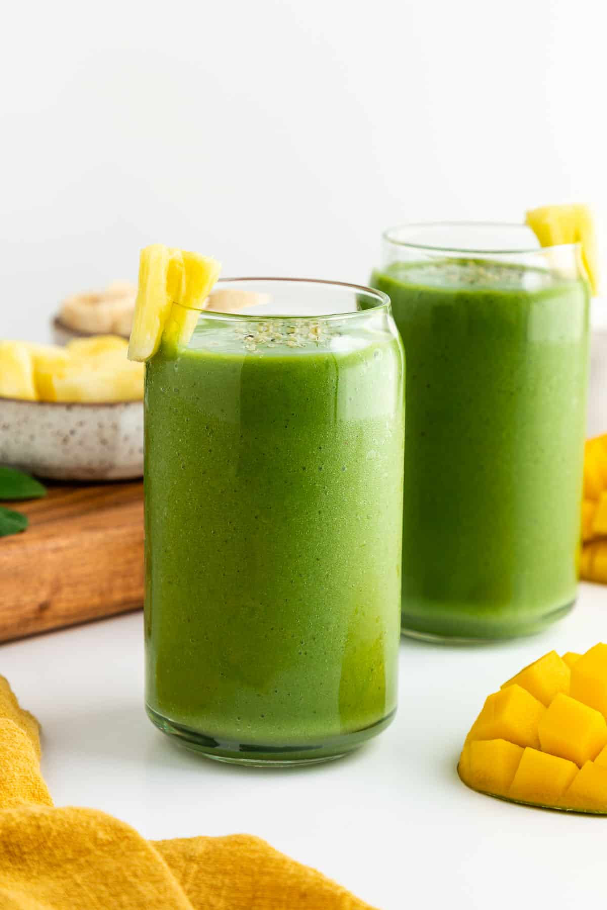 two green smoothies inside glasses beside a bowl of pineapple, two mangoes, and a yellow linen napkin