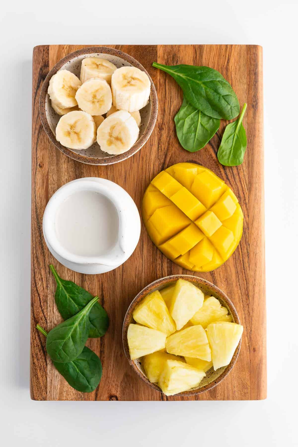 a dark wood rectangular board with a sliced mango, bowl of chopped banana, bowl of pineapple chunks, glass of almond milk, and fresh spinach on top