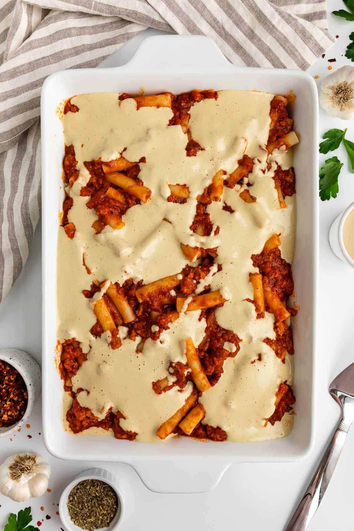 a white casserole dish with marinara sauce, ziti sauce, and cashew cream inside it