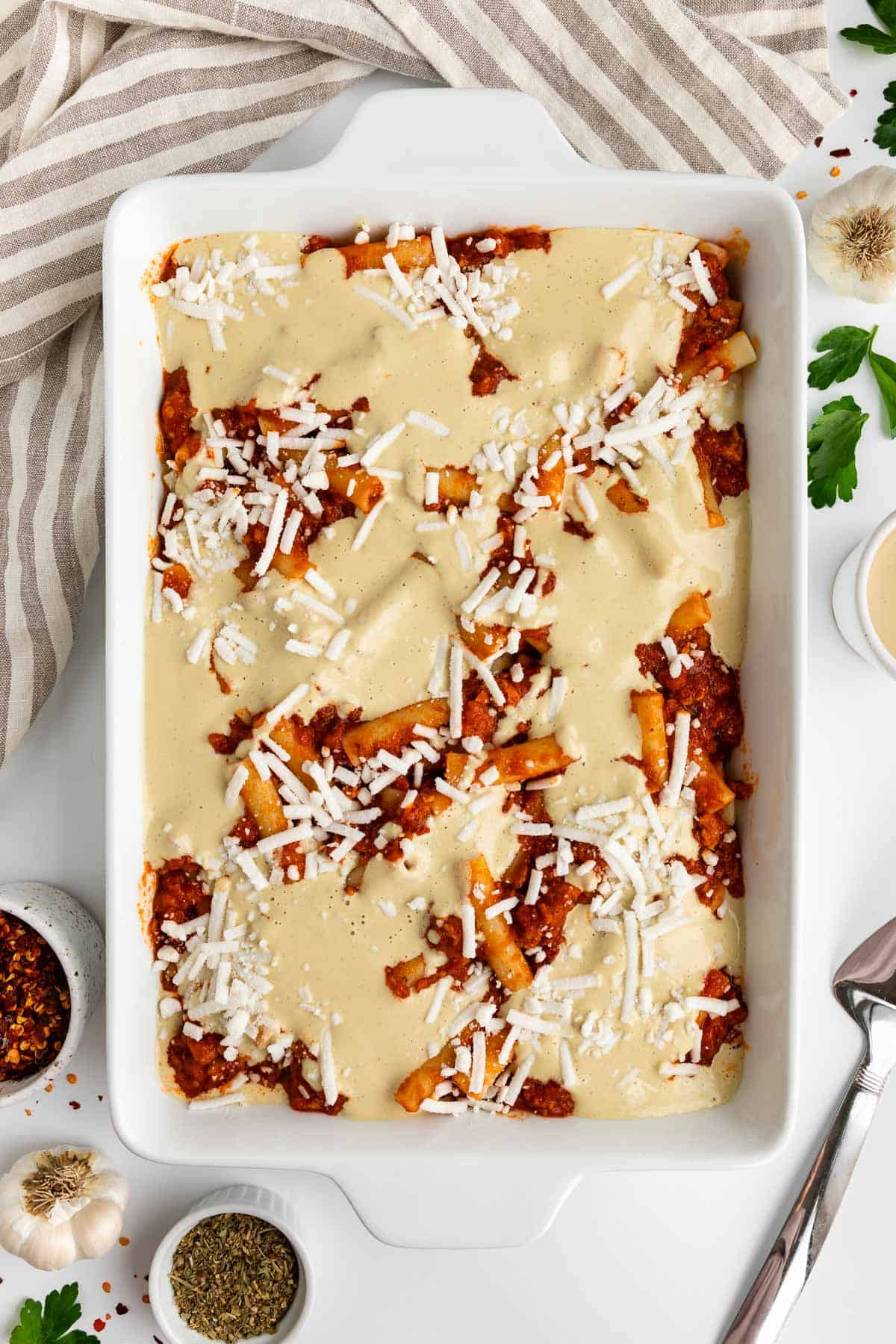 a white casserole dish with marinara sauce, ziti sauce, cashew cream, and vegan mozzarella inside it
