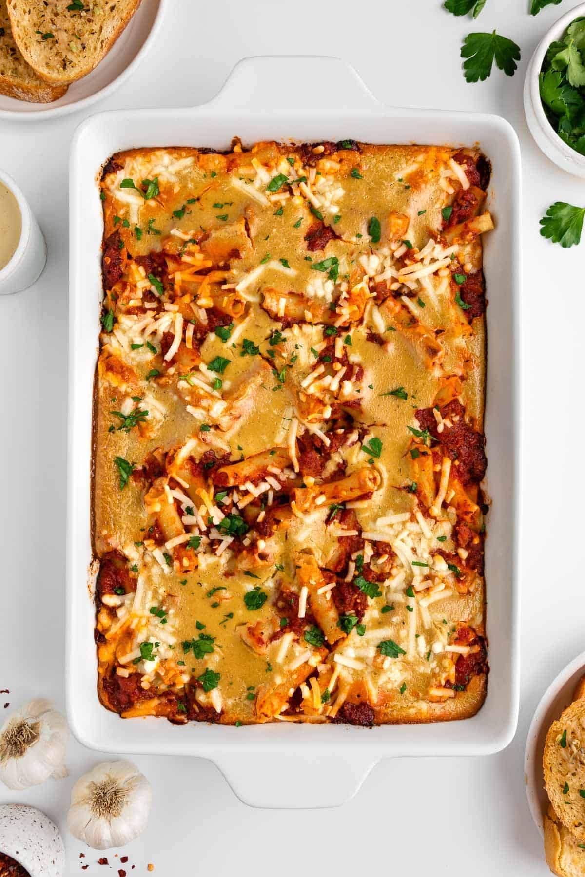vegan baked ziti inside a white casserole dish surrounded by garlic cloves, fresh parsley, and garlic bread