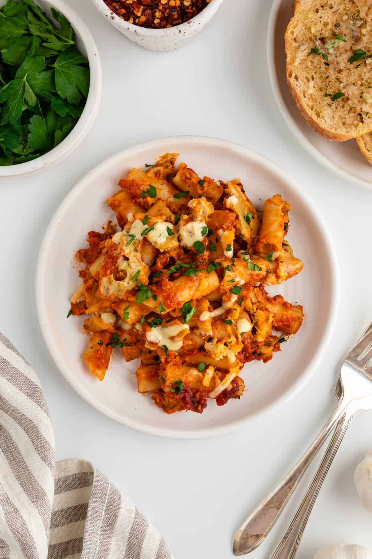 a serving of vegan baked ziti on a white plate surrounded by a striped linen napkin, two forks, a bowl of fresh parsley, a bowl of crushed red pepper, and vegan garlic bread