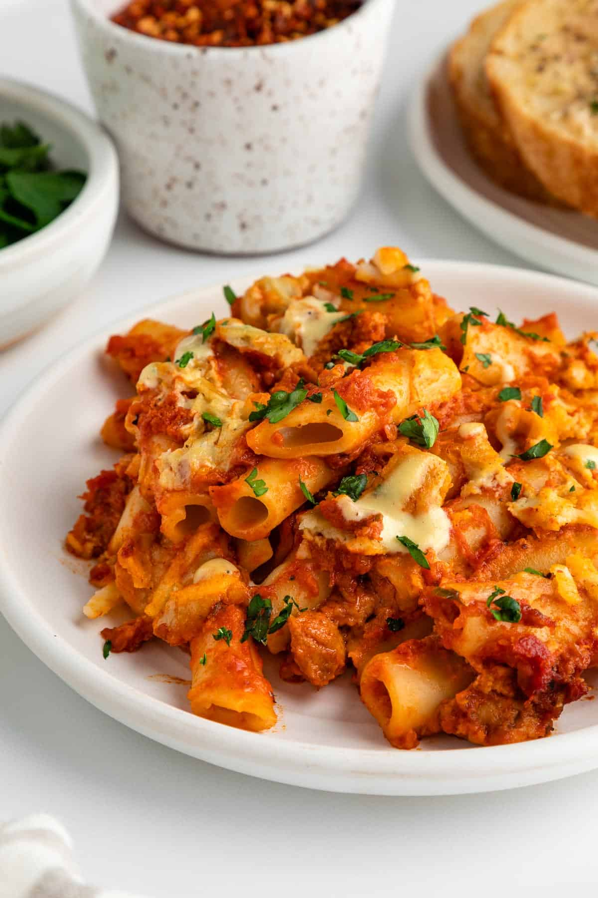 a close up image of vegan baked ziti on a white plate