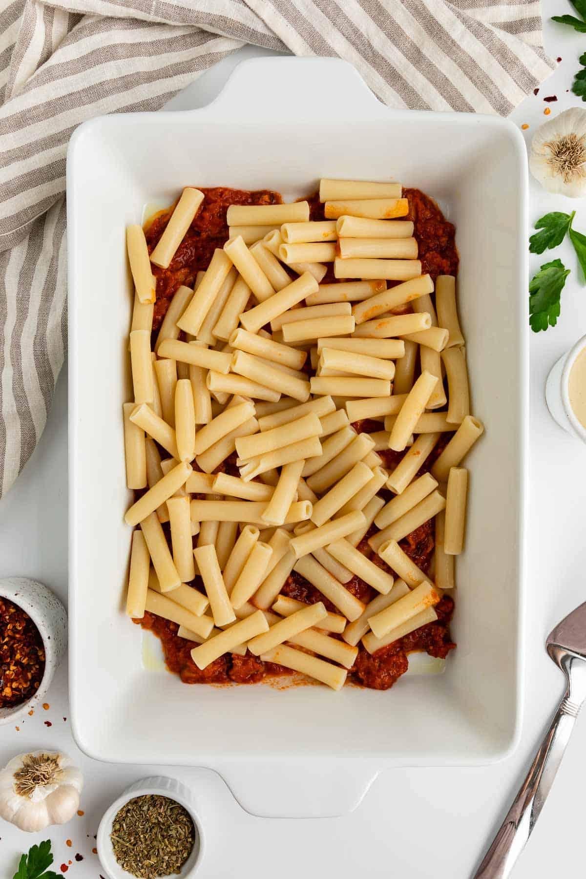 a white casserole dish with marinara sauce and ziti pasta in it