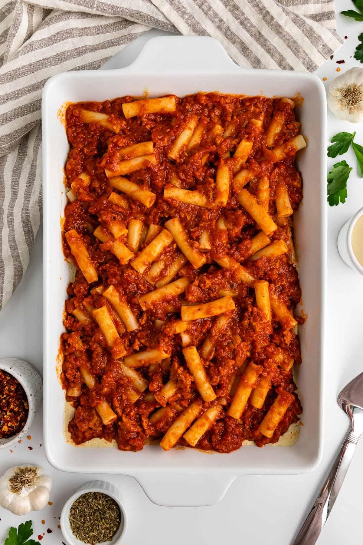 ziti pasta and marinara sauce mixed together inside a white casserole dish