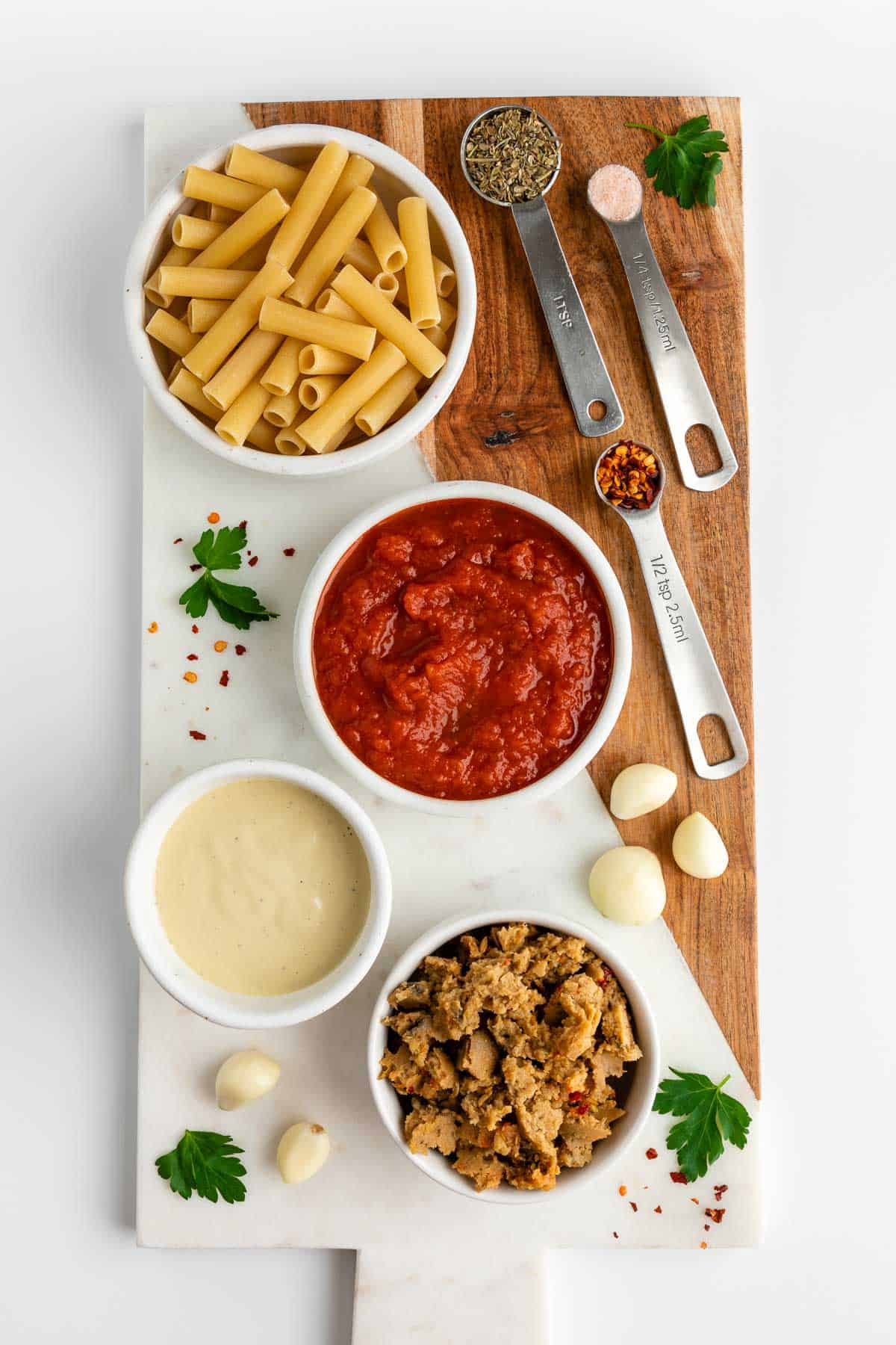 a wood and marble serving board topped with a bowl of marinara sauce, vegan sausage, cashew cream, ziti pasta, garlic cloves, fresh parsley, crushed red pepper flakes, and salt