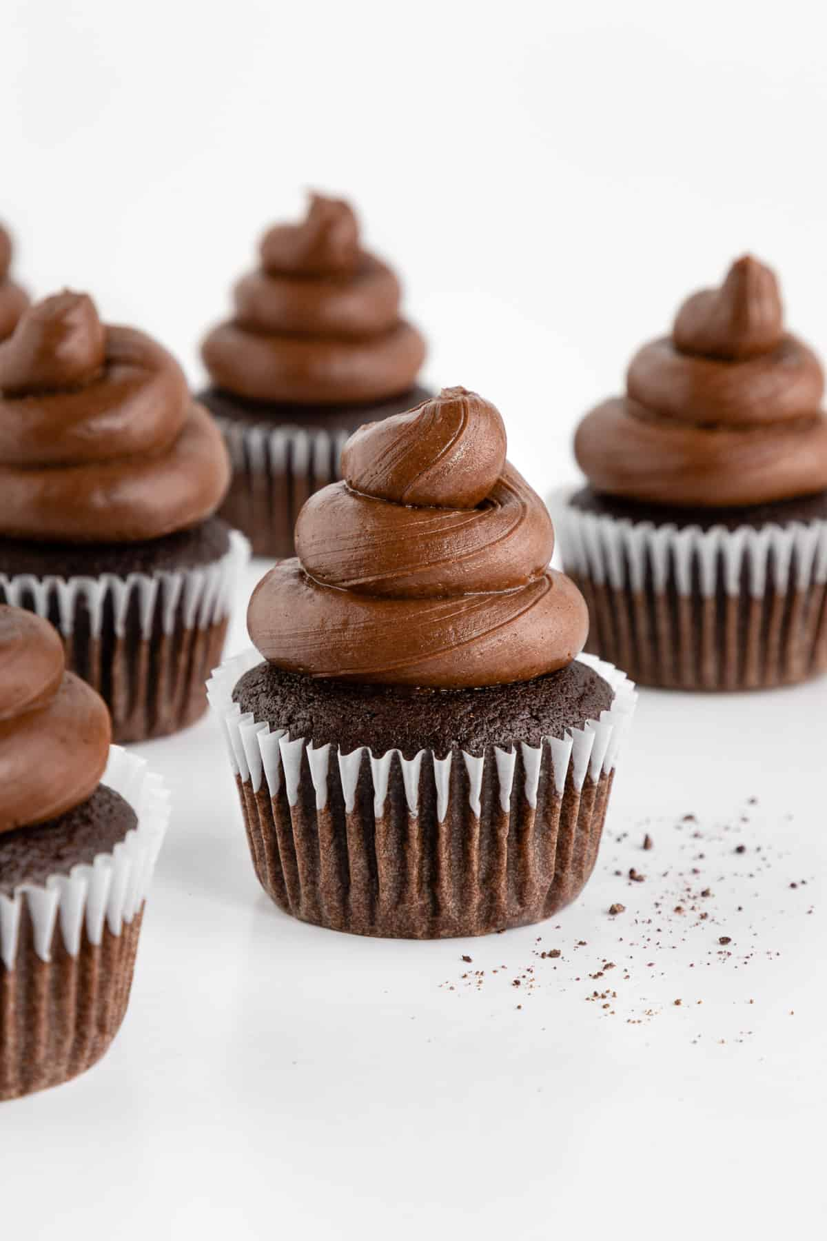 five vegan chocolate cupcakes with chocolate buttercream frosting on top
