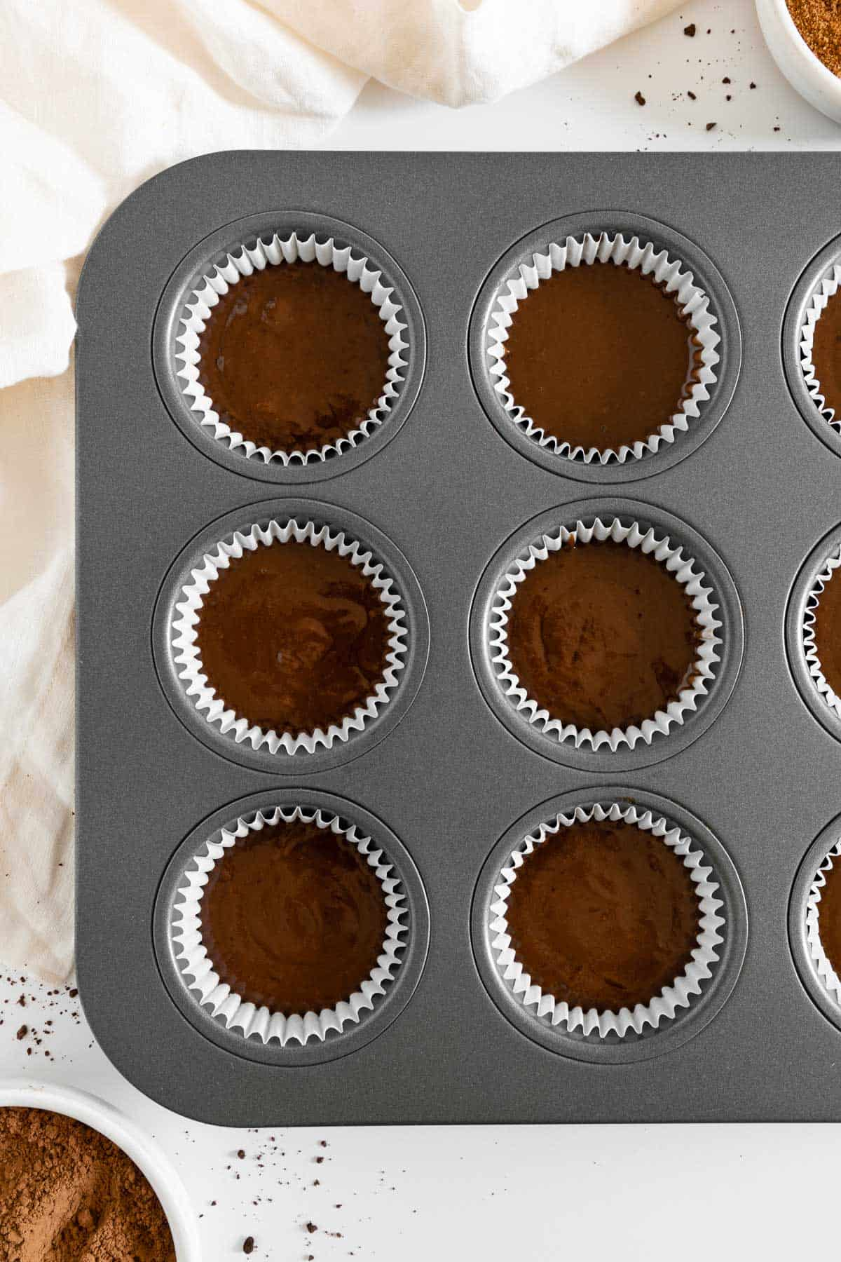 a muffin tin filled with cupcake liners and chocolate cake batter inside them