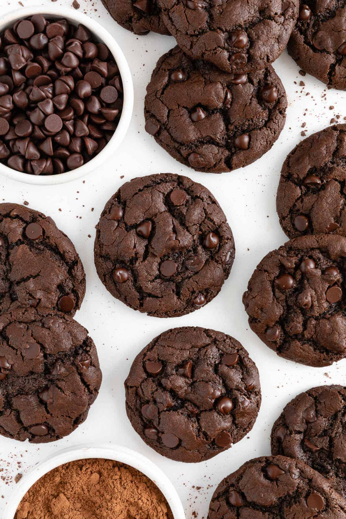 several warm and gooey vegan double chocolate chip cookies laying on white parchment paper