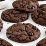 vegan double chocolate chip cookies on a white surface beside a bowl of cocoa powder and another bowl of chocolate chips