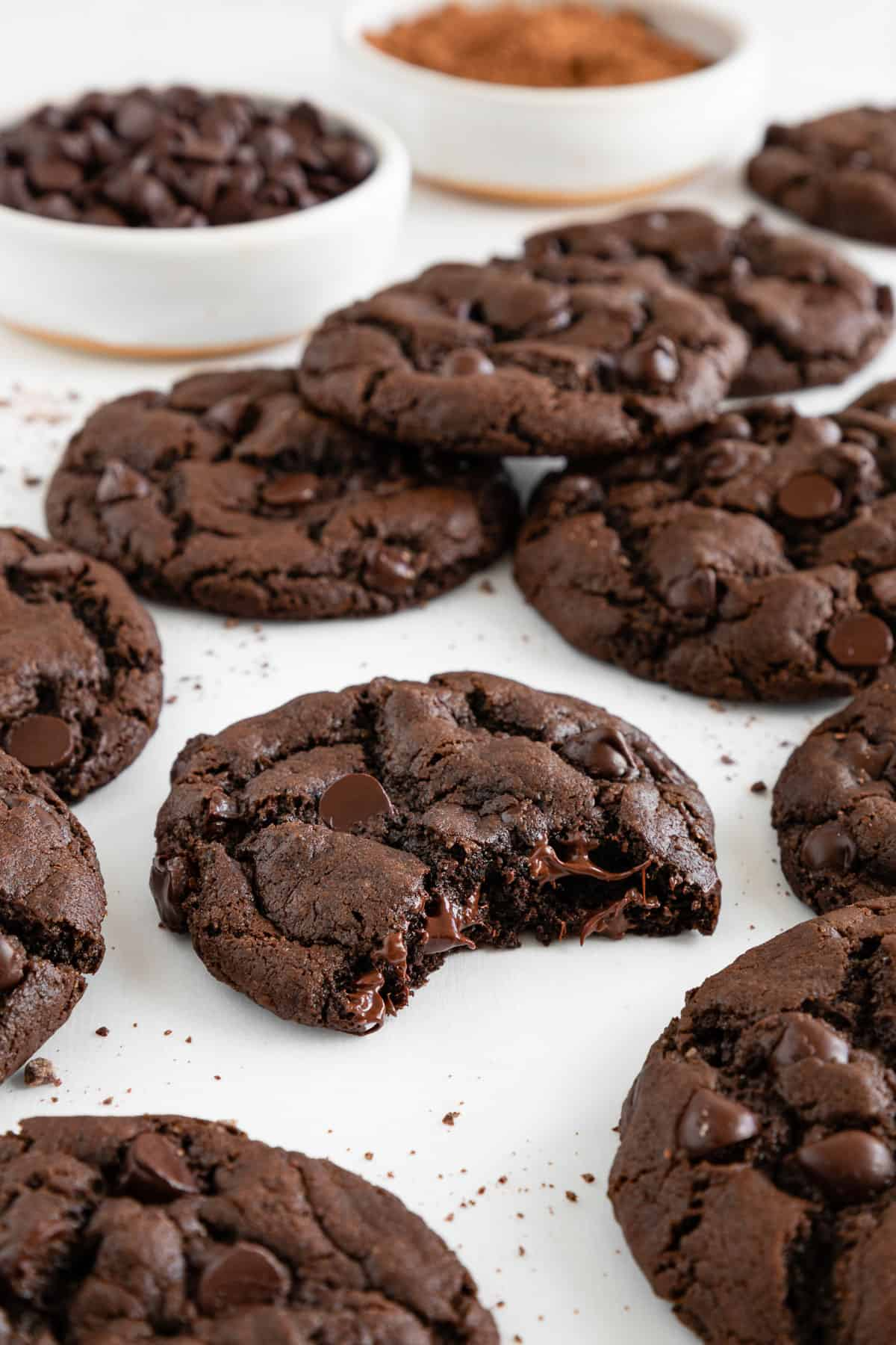 a gooey vegan double chocolate chip cookie with a bite taken out of it, surrounded by a dozen more cookies and a bowl of cocoa powder