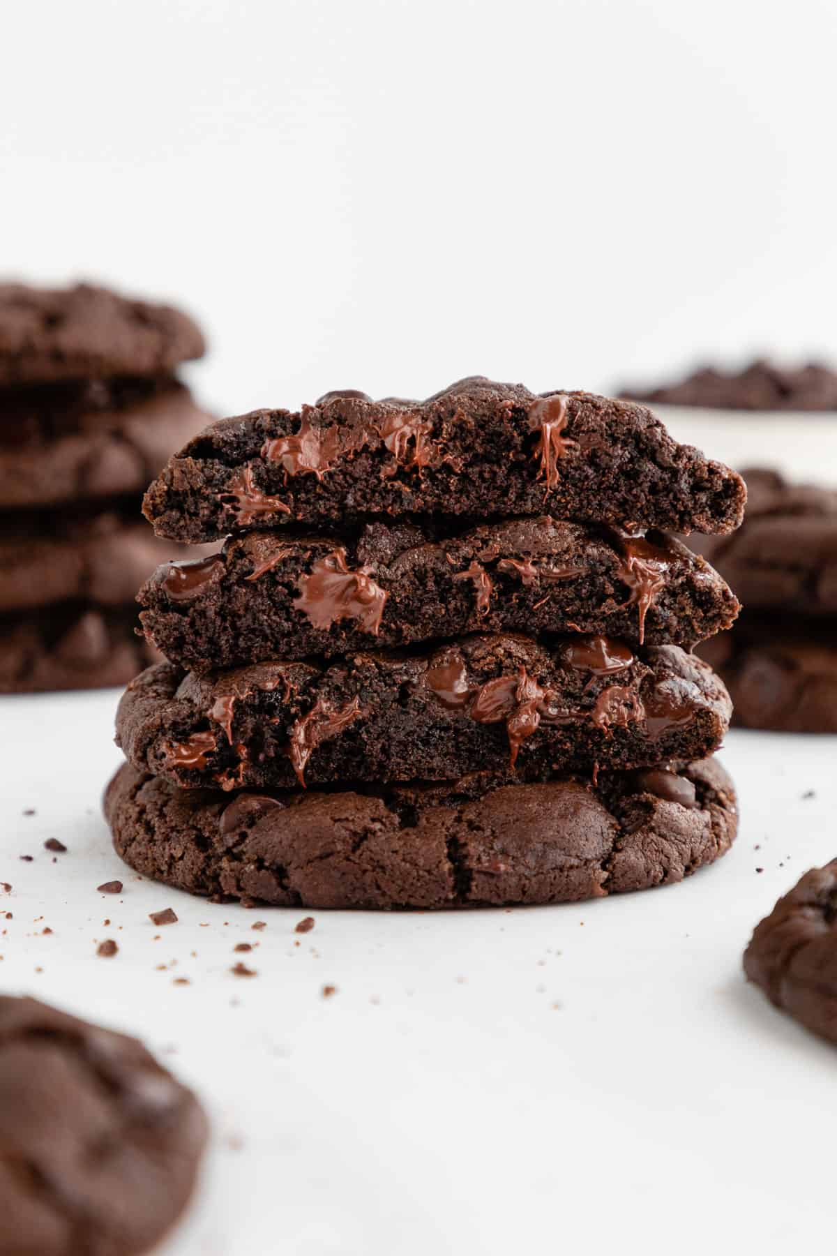 a warm and gooey stack of four vegan double chocolate chip cookies with melted chocolate oozing out of the middle