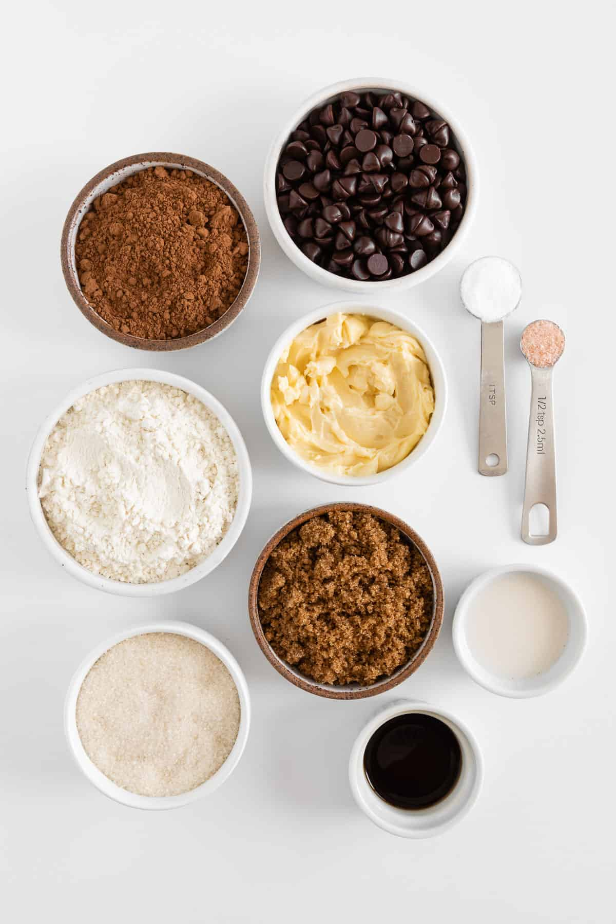 small white bowls filled with chocolate chips, cocoa powder, flour, vegan butter, sugar, brown sugar, vanilla extract, and non-dairy milk