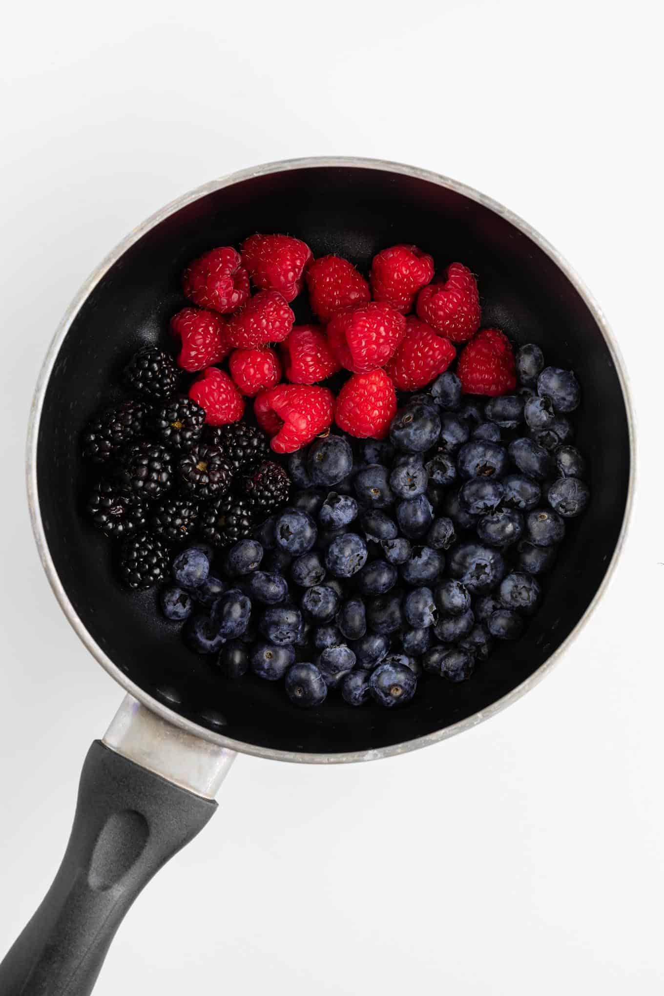 blueberries, raspberries, and blackberries inside a black sauce pot