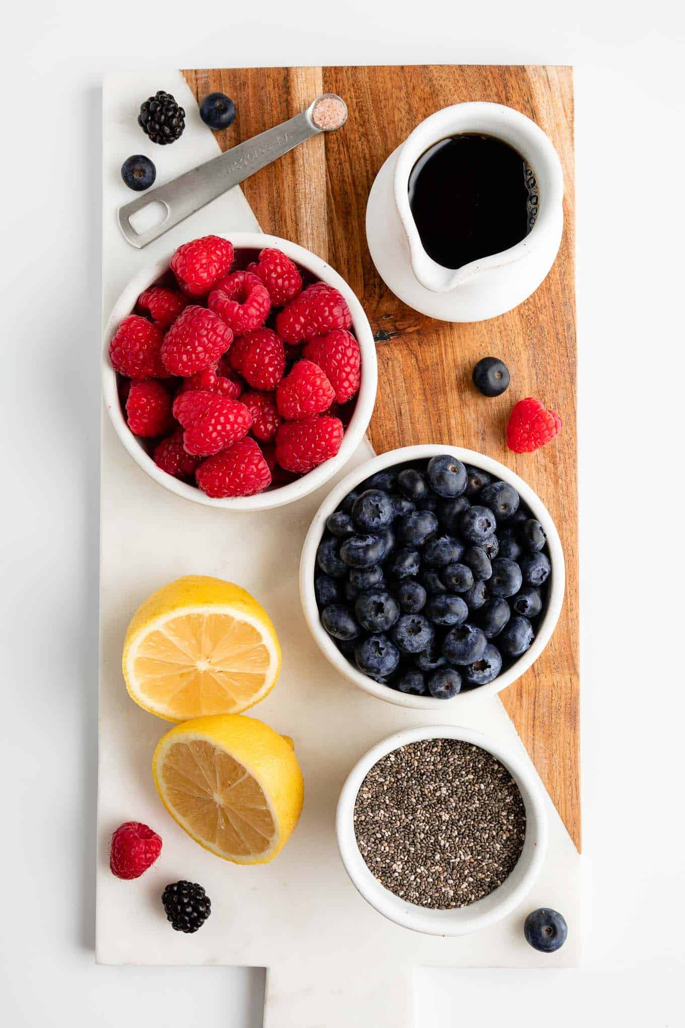 serving board topped with a bowl of blueberries, a bowl of raspberries, a sliced lemon, chia seeds, and pitcher of maple syrup