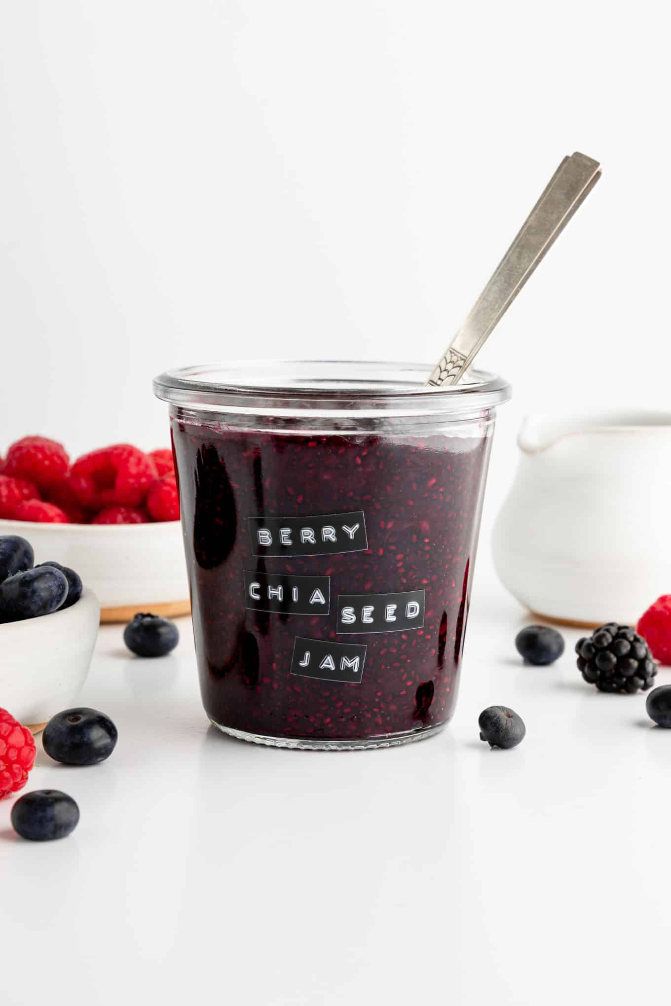 a weck jar filled with berry chia seed jam beside bowls filled with mixed berries