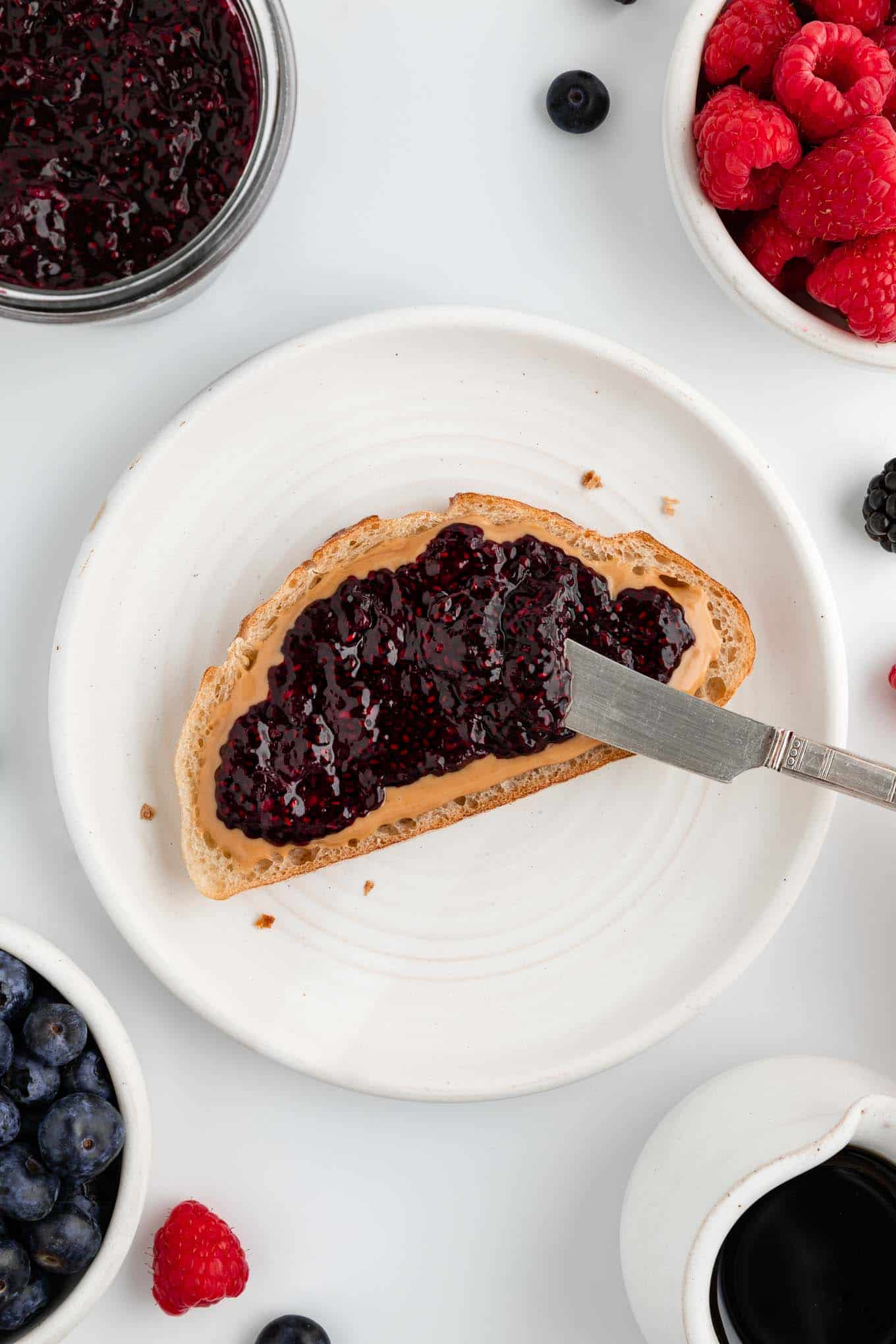 a knife spreading berry chia jam on peanut butter toast on a white plate