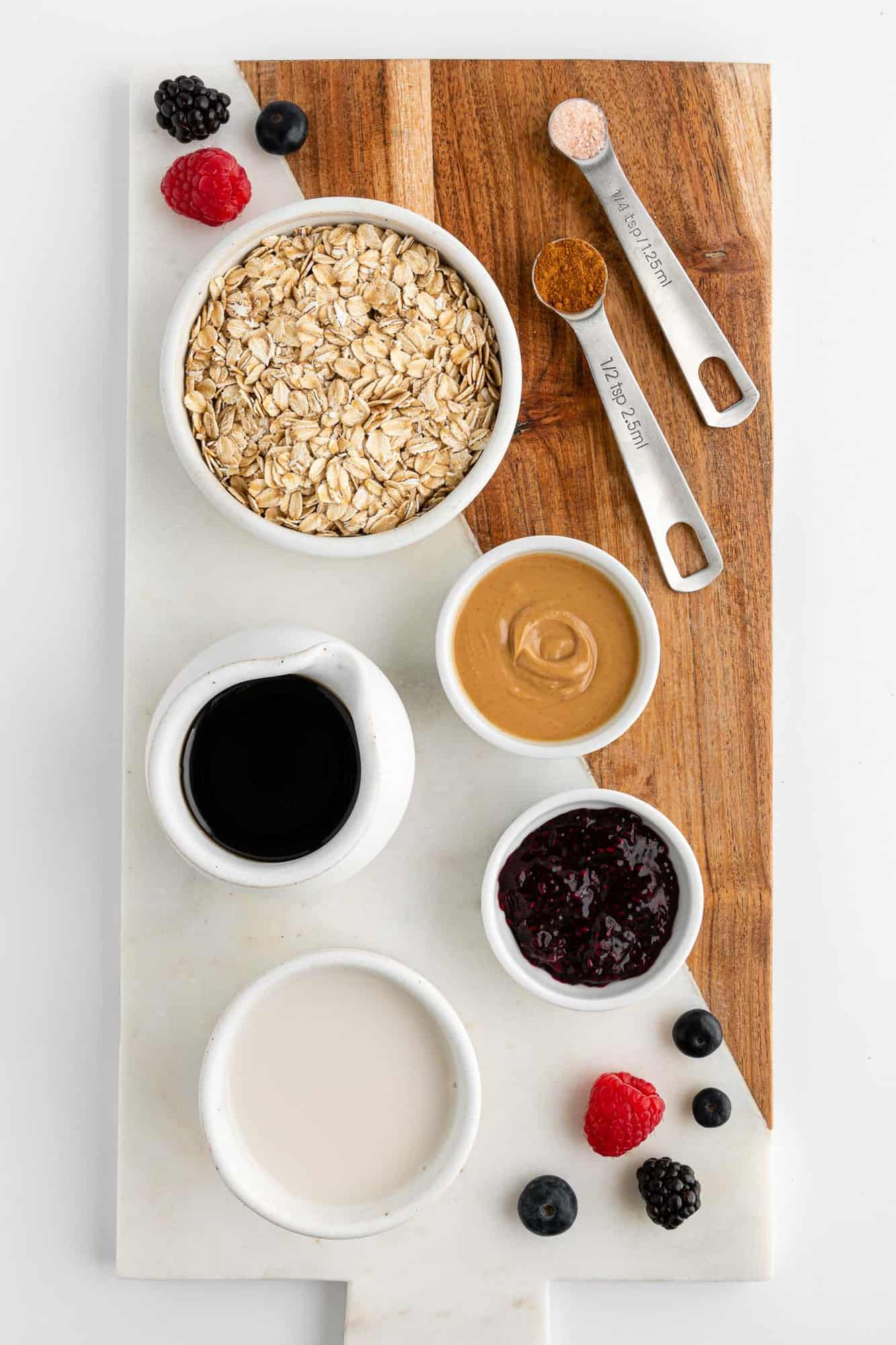 a wooden and marble serving board topped with ingredients for pb&j oatmeal, including oats, almond milk, maple syrup, and berry jam